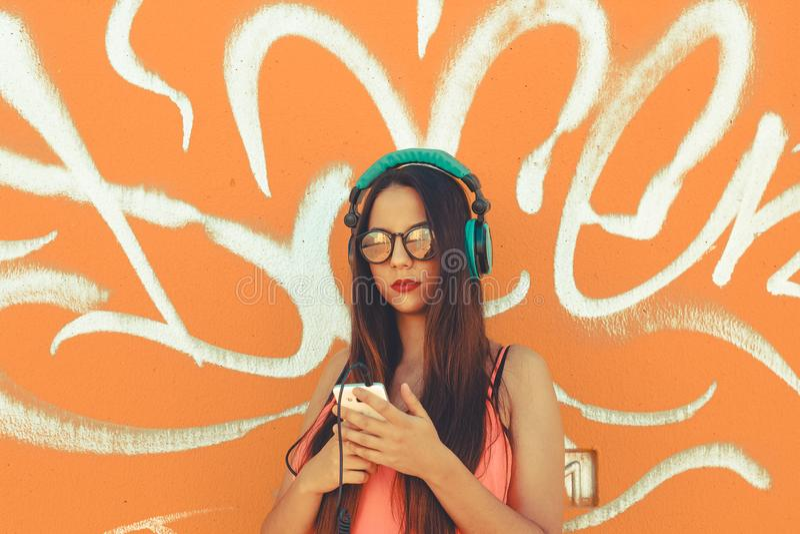 Uma jovem senhora elegante que usa seu telefone celular para escutar música com seus fones de ouvido foto de stock