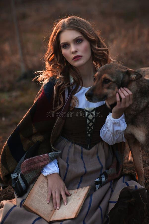 Uma jovem senhora em um vestido medieval com um cão e um livro imagens de stock