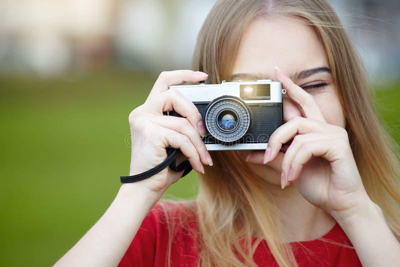 Uma jovem sorridente segurando uma câmera de retrô velha e tirando fotos, espaço para cópia, fotógrafo amador, verão ensolarado fotos de stock