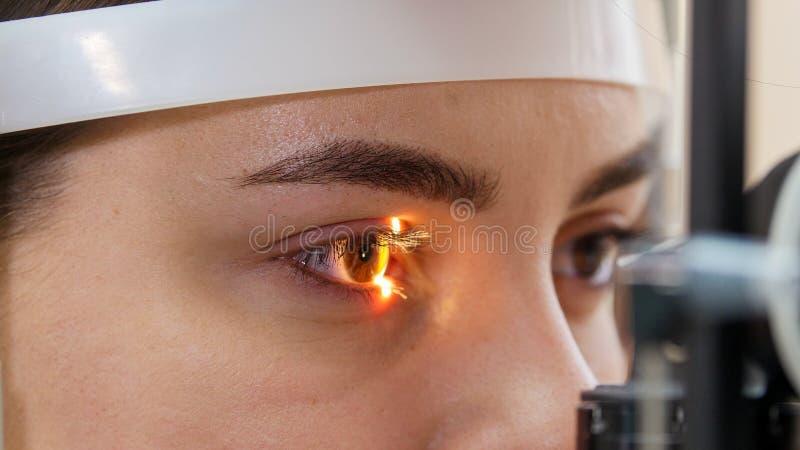 Uma jovem a verificar a sua acuidade visual com uma luz de uma grande máquina de optometria especial - cor castanha e nebulosa fotos de stock