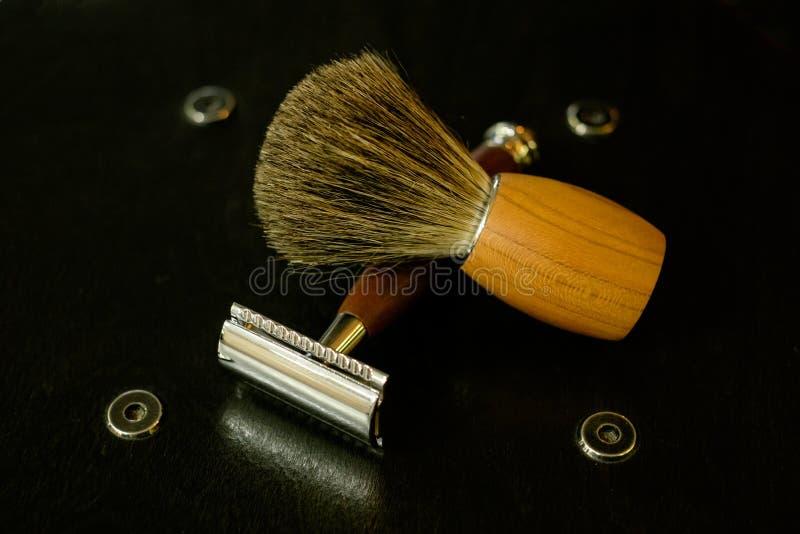 Uma lâmina de aço tradicional com um punho marrom da madeira preciosa e uma escova de rapagem em um fundo de madeira natural fotografia de stock royalty free