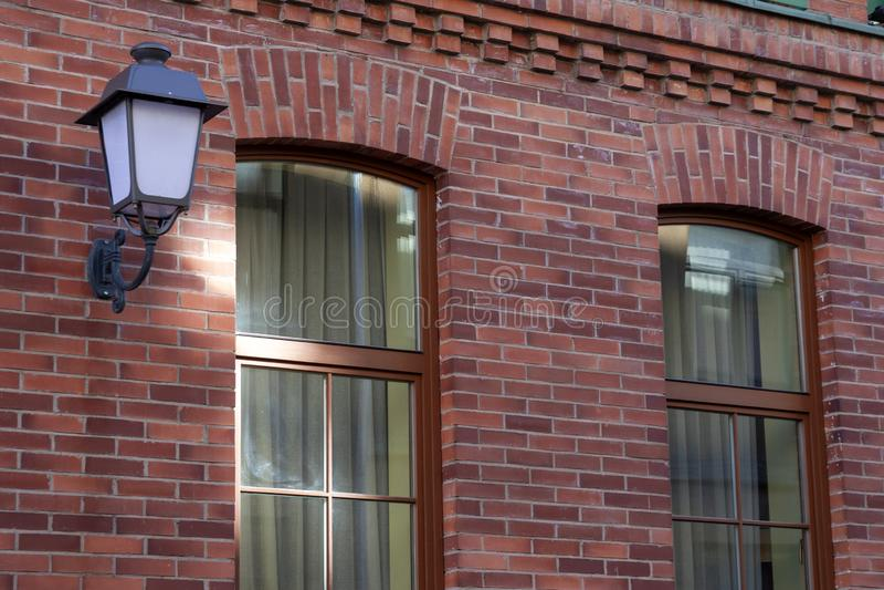 Uma lâmpada de rua bonita em uma parede de tijolo vermelho fotografia de stock royalty free