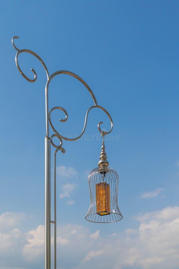 Uma lâmpada de vidro amarela pendura acima a lâmpada inoxidável da rua forte que o sol reflete no céu azul inferior inoxidável co imagens de stock