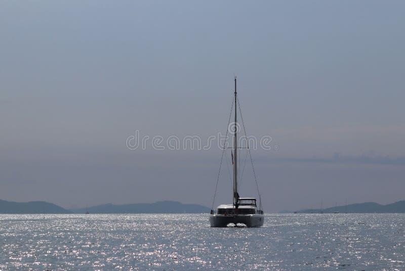 Uma lagoa 450 do catamarã da navigação do cruzeiro com um chalupa-tipo equipamento de Bermuda vai após as ilhas do Riviera croata foto de stock