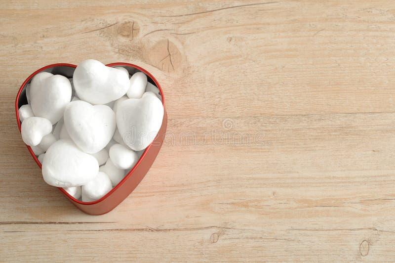 Uma lata vermelha da forma do coração encheu-se com os corações fotografia de stock