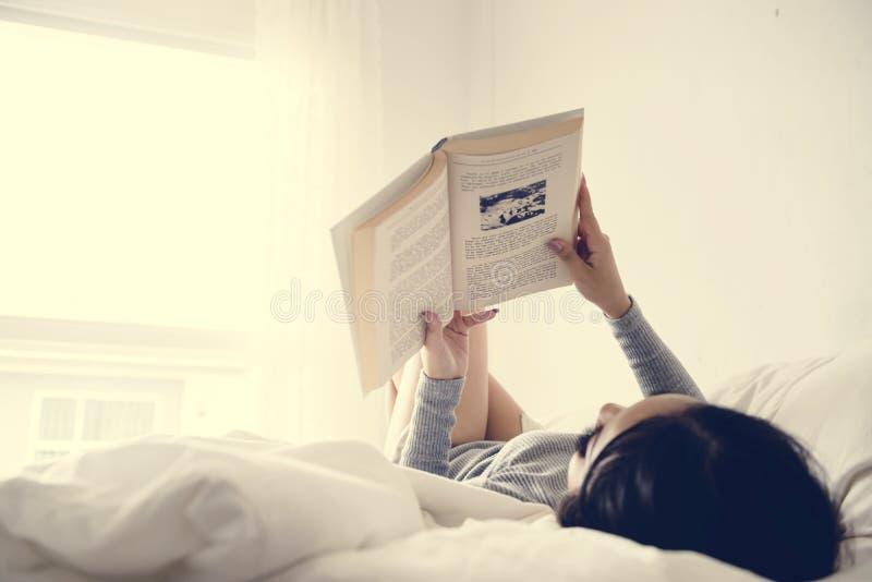 Uma leitura asiática da mulher em uma cama em uma sala mínima brilhante foto de stock