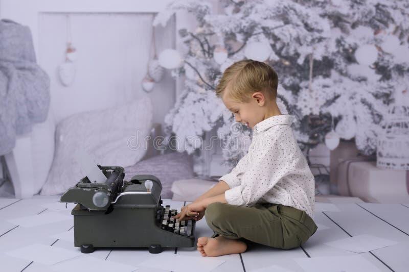 Uma letra a Papai Noel Uma letra a Papai Noel Uma criança feliz redige uma lista de presente fotografia de stock royalty free