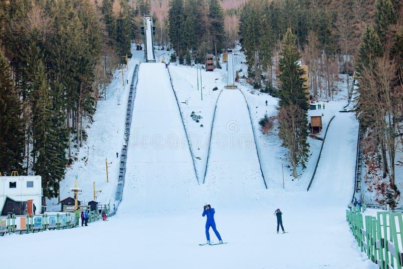 Uma ligação em ponte de esqui que voa de uma torre do monte do salto de esqui fotos de stock royalty free