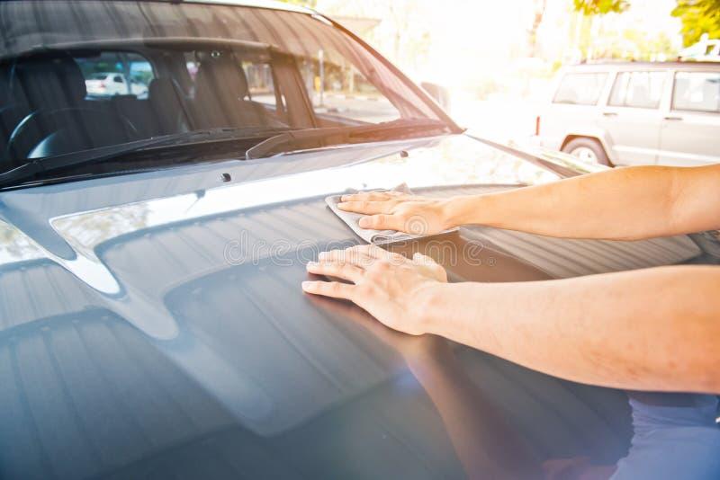 Uma limpeza limpa o carro com o pano e o lustro encerando o creme foto de stock royalty free