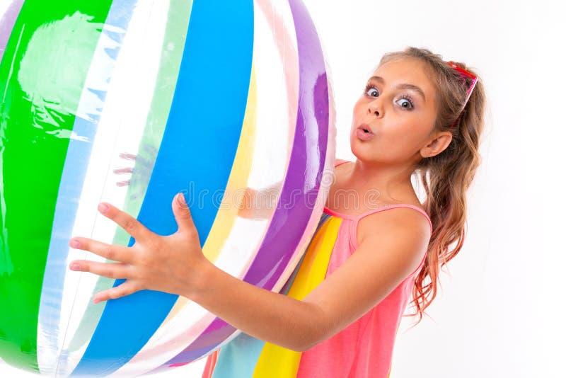 Uma linda garota segura uma bola inflável e colorida e é sacudida foto de stock royalty free