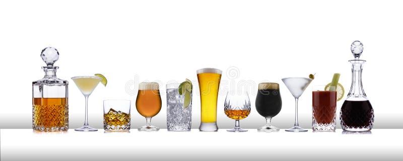 Uma linha de bebidas alcoólicas de uísque a lager, em uma linha, em uma barra branca como a superfície imagem de stock