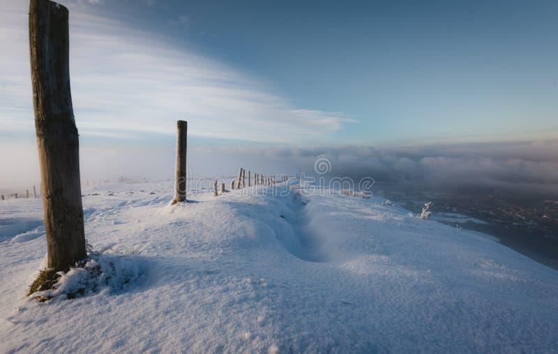 Uma linha de cargos de madeira abaixo de um monte nevado no vale abaixo coberto na névoa imagem de stock