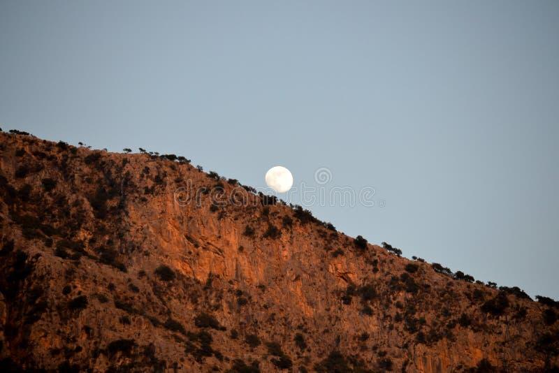 Uma Lua cheia aumenta sobre as montanhas C?u da noite fotografia de stock