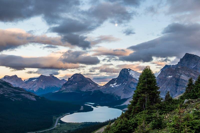 Uma Lua cheia pendura sobre o lago bow e o pico da curva da medicina em Banff N fotos de stock