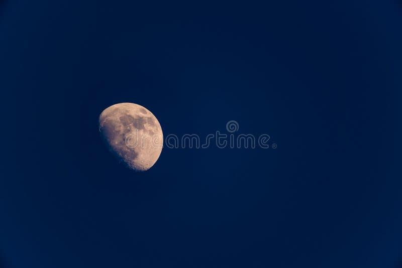Uma lua dos três quartos na noite fotografia de stock