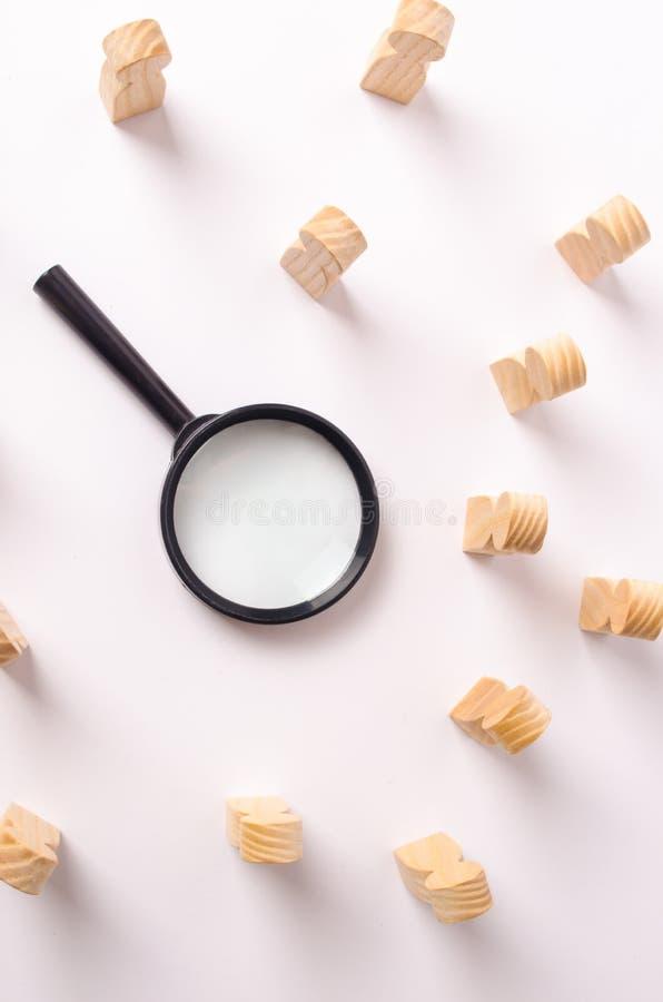 Uma lupa encontra-se no centro das figuras de madeira dos povos que a olham O conceito da busca para trabalhadores fotografia de stock