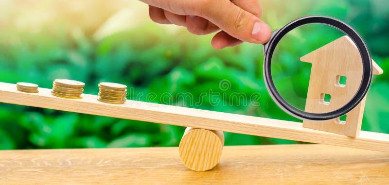 Uma lupa explora uma pilha de moedas em escalas e em uma casa de madeira Pagamento mensal do aluguel Conceito 6 dos bens imobiliá foto de stock
