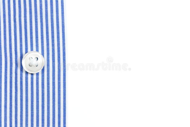 Uma luva de uma camisa listrada azul com um botão no fundo branco imagens de stock