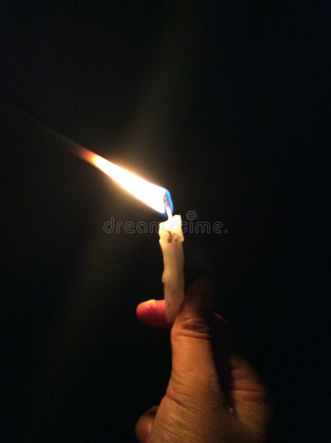 Uma luz da vela na escuridão foto de stock