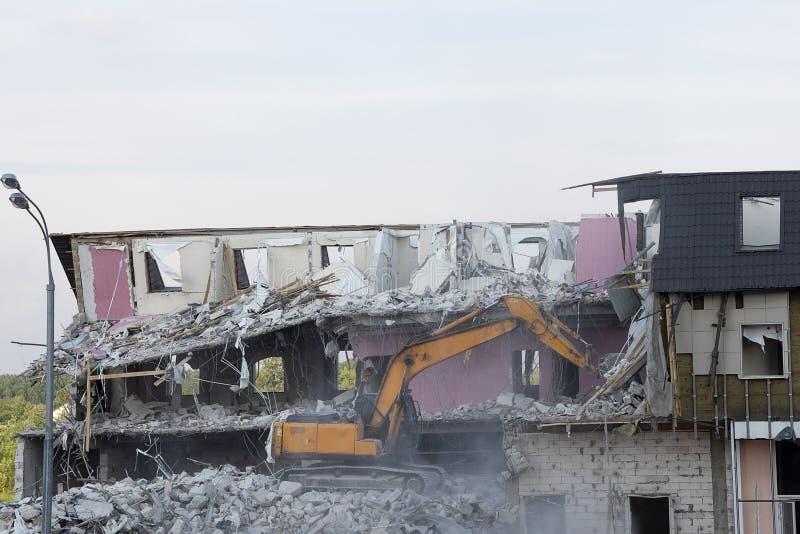 Uma máquina escavadora demole uma construção do multi-andar com uma concha A técnica destrói a construção, é encaixes, concreto e fotos de stock