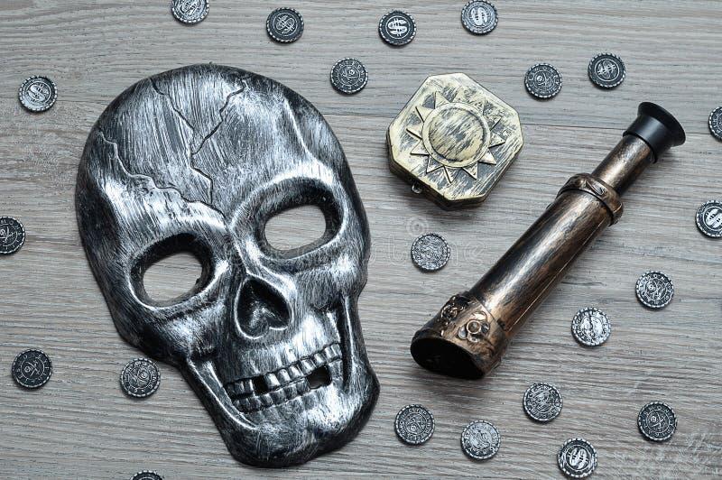 Uma máscara do crânio, o compasso e um monóculo com brinquedo pirateiam moedas foto de stock royalty free