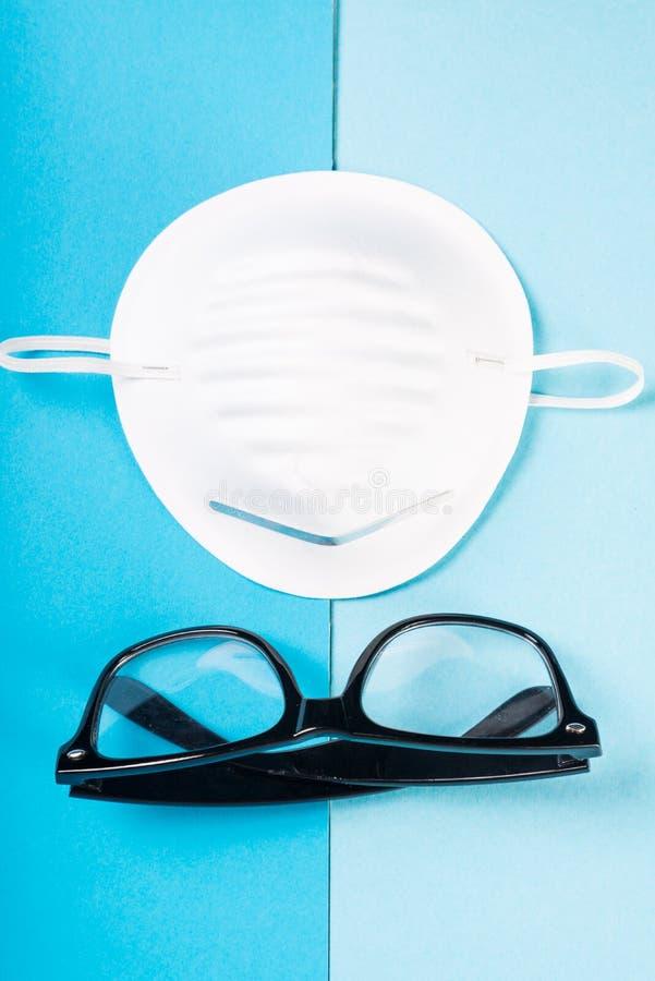 Uma máscara protetora no fundo azul com vidros foto de stock