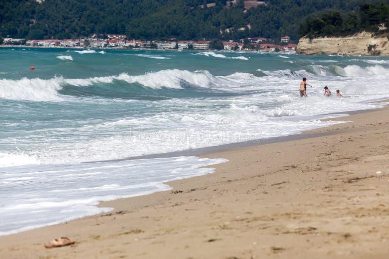 Uma mãe ajuda suas crianças a apreciar a praia imagens de stock royalty free