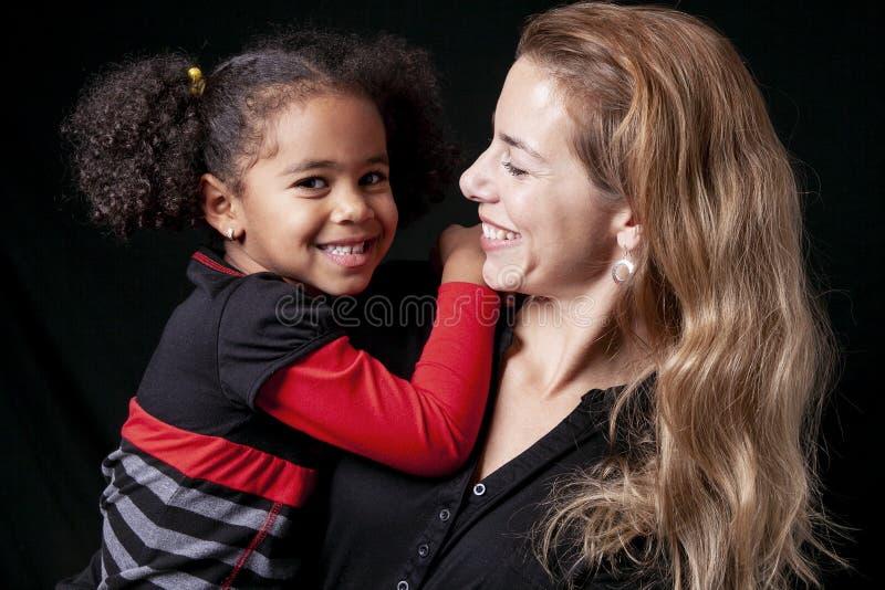 Uma mãe da família com a criança da menina que levanta em um estúdio preto do fundo imagens de stock