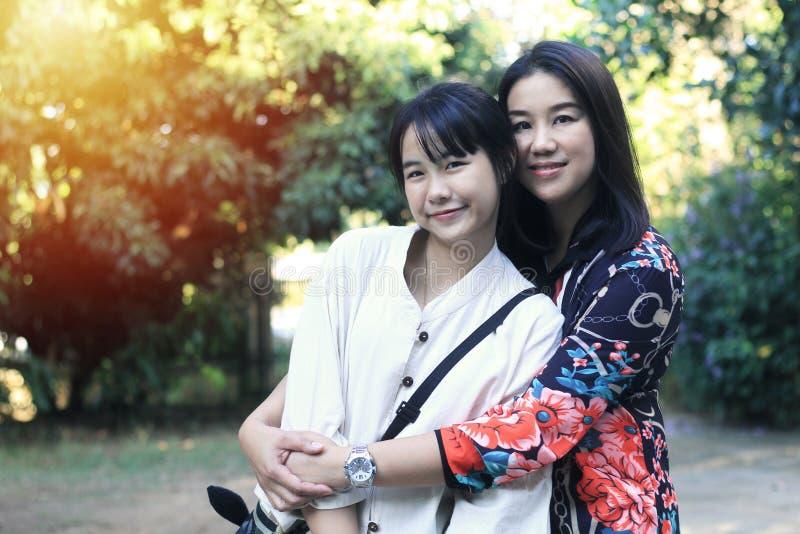 Uma mãe e uma criança asiáticas bonitos estão estando em uma posição diferente imagens de stock