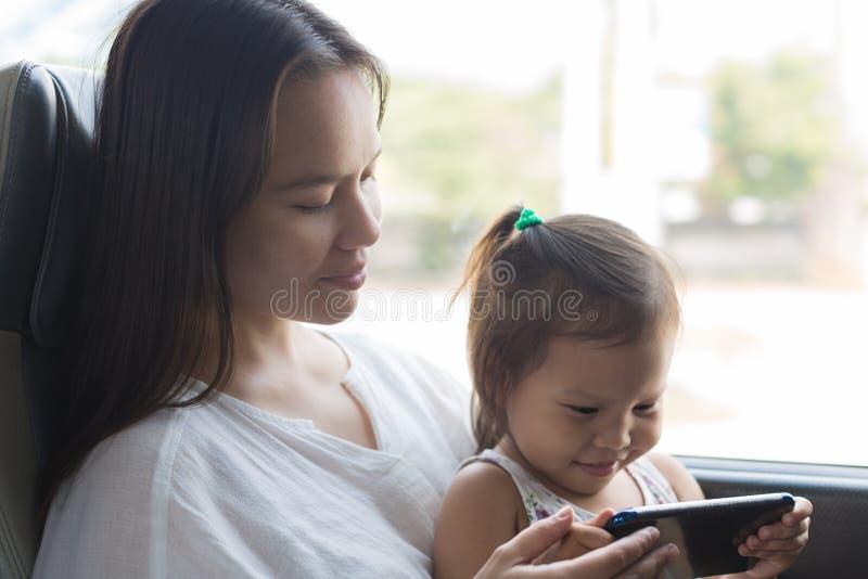 Uma mãe e uma criança que olham a tevê no trem, viajando junto foto de stock