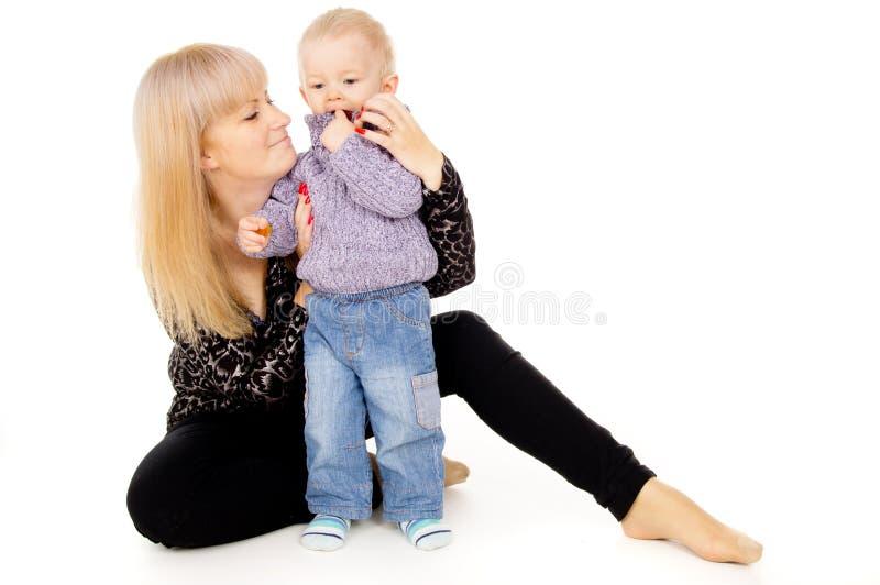 Uma mãe feliz senta-se com seu bebê pequeno imagem de stock royalty free