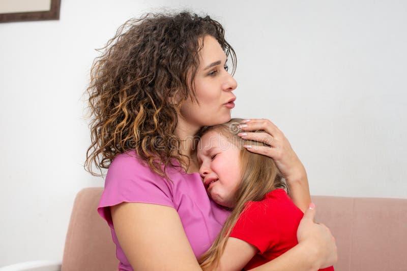 Uma mãe nova acalma sua filha A menina está gritando e sua mãe abraçou-a com amor imagem de stock royalty free