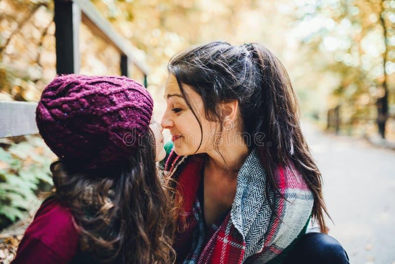 Uma mãe nova com uma filha da criança que toca nos narizes na floresta na natureza do outono foto de stock