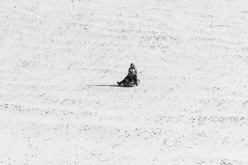 Uma mãe nova com uma filha pequena monta em uma tubulação sledding inflável em uma inclinação da neve, foto preto e branco foto de stock