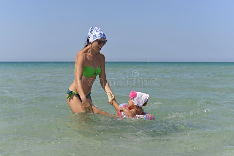 Uma mãe nova com uma nadada pequena da filha no mar foto de stock