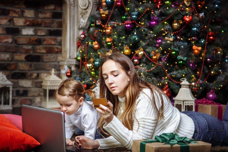 Uma mãe nova com os presentes de uma compra da filha usando o portátil e o cartão de crédito O conceito da preparação pelo Natal  imagem de stock royalty free