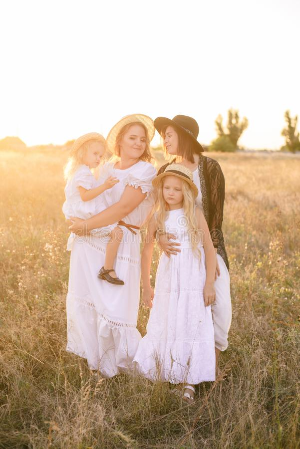 Uma mãe nova com suas filhas e uma tia com cabelo louro nos vestidos brancos no por do sol no verão em um campo do campo imagens de stock royalty free