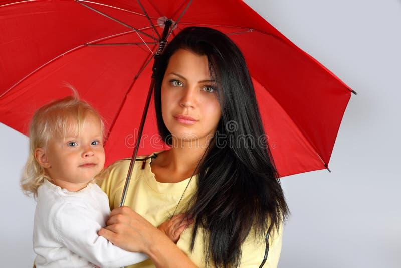 Uma mãe nova com um bebê sob o guarda-chuva vermelho imagem de stock