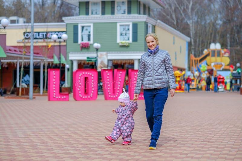 Uma mãe nova feliz anda através do quadrado pela mão com sua filha pequena As pessoas incandescem com felicidade imagens de stock royalty free