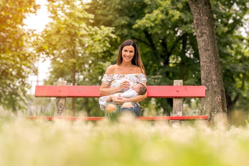 Uma mãe nova que senta-se em um banco e que alimenta seu bebê fotografia de stock