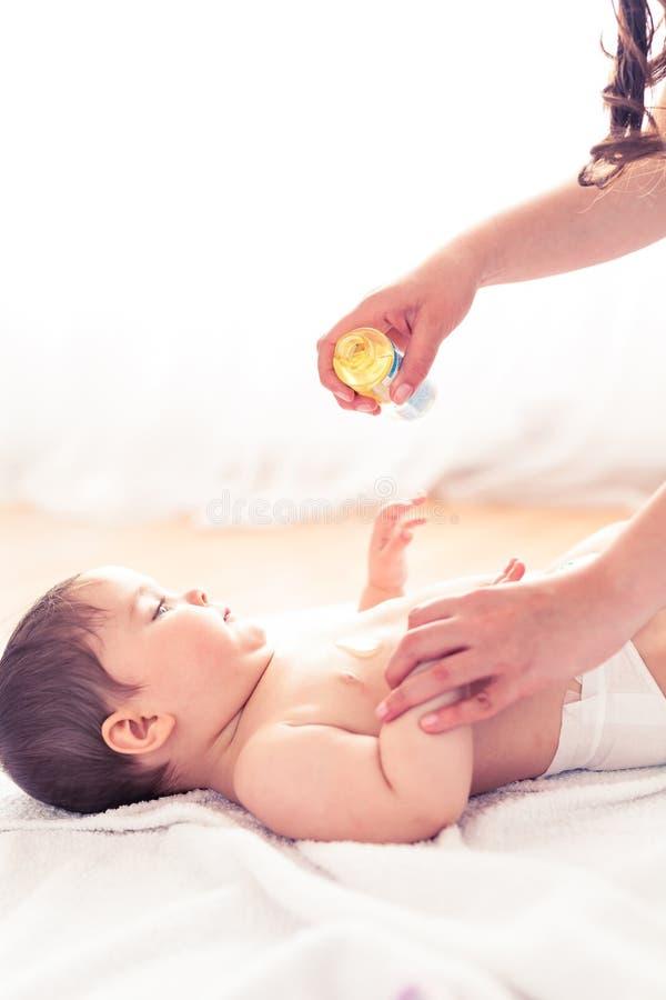 Uma mãe que faz massagens um bebê com óleo fotos de stock royalty free