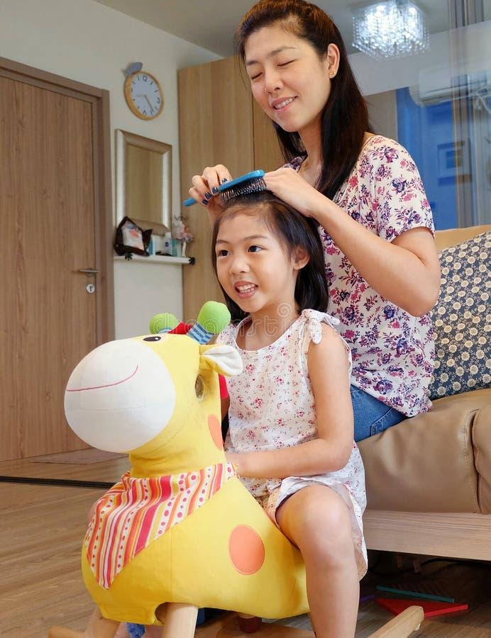 Uma mãe que penteia seu cabelo do ` s da filha imagens de stock