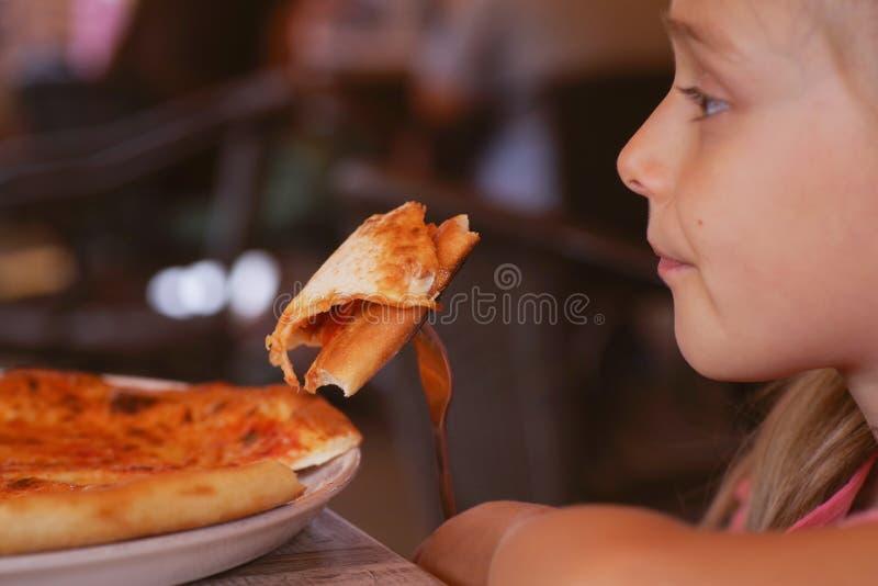 Uma mão bonita pequena da menina que guarda uma fatia de pizza no restaurante imagens de stock royalty free