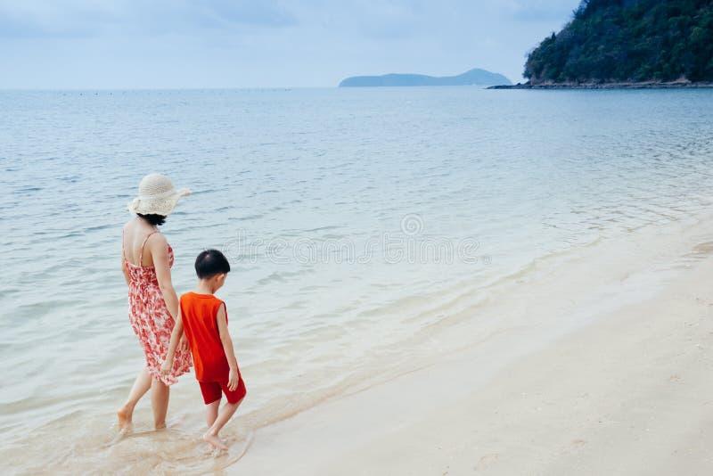 Uma mão da terra arrendada da mãe e do filho e passeio no ar livre da praia e do mar no por do sol fotografia de stock royalty free