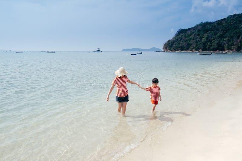 Uma mão da terra arrendada da mãe e do filho e passeio no ar livre da praia e do mar no por do sol fotos de stock