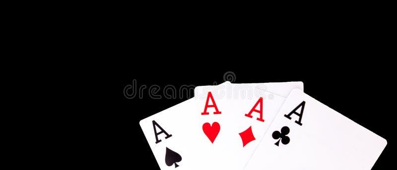 Uma mão de pôquer de vencimento de quatro ternos dos cartões de jogo dos áss no fundo preto foto de stock