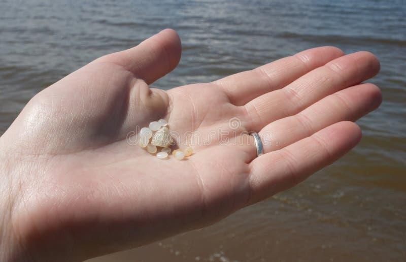 Uma mão de pedras da areia da terra arrendada da mulher foto de stock royalty free