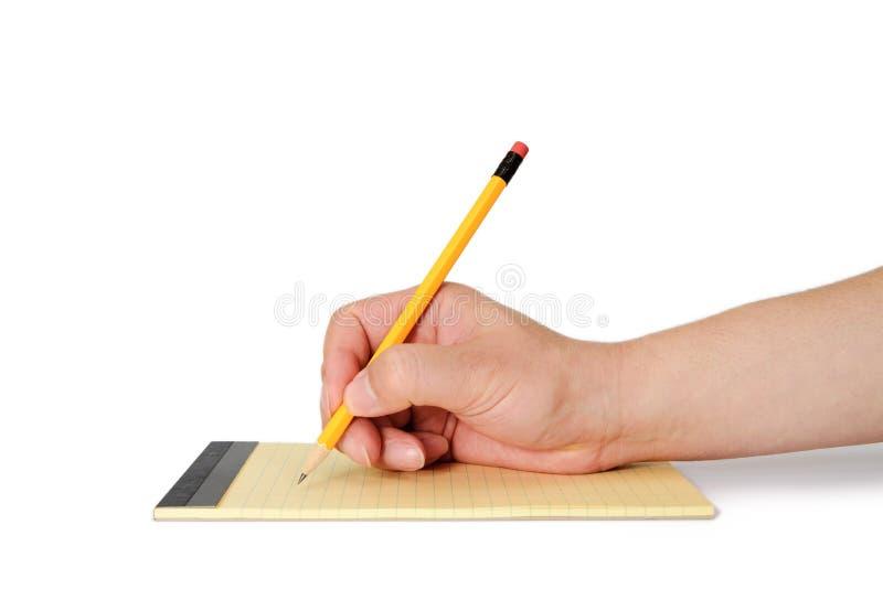 Uma mão do homem que guarda um lápis sobre notas fotos de stock