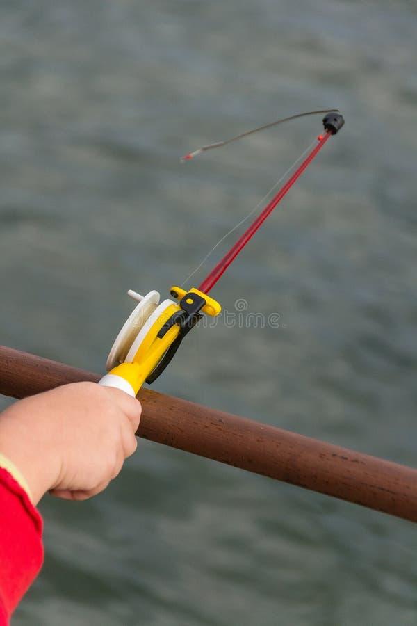 Uma mão do ` s da criança está pescando em uma vara de pesca pequena Pesca de Ozernaya fotografia de stock royalty free