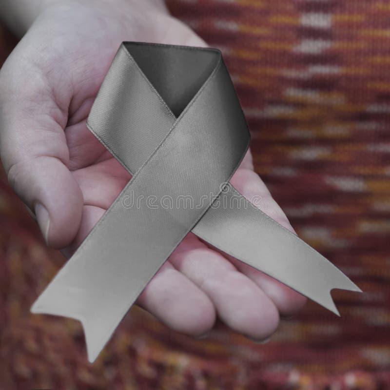 Uma mão do ` s da mulher com uma fita cinzenta da conscientização de di do ` s de Parkinson imagens de stock